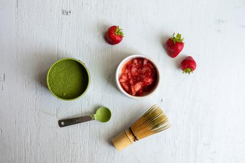 Open tin of Amai Matcha next to a bowl of muddled strawberries, with a teaspoon of matcha and matcha whisk below