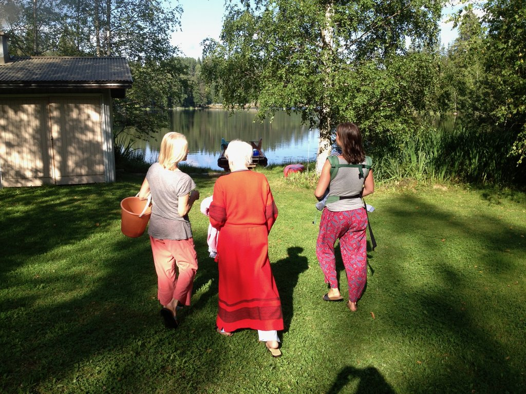 Sarah Scarborough (right) walking toward a lake in Finland with her grandmother (center) and mother (left)