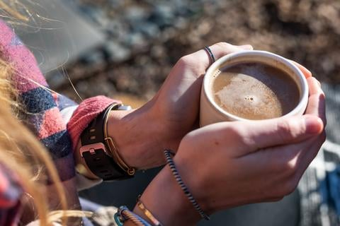 Woman wrapped in a blanket holding a cup of chai tea