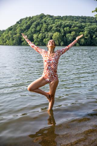 Woman doing a yoga pose standing in a lake