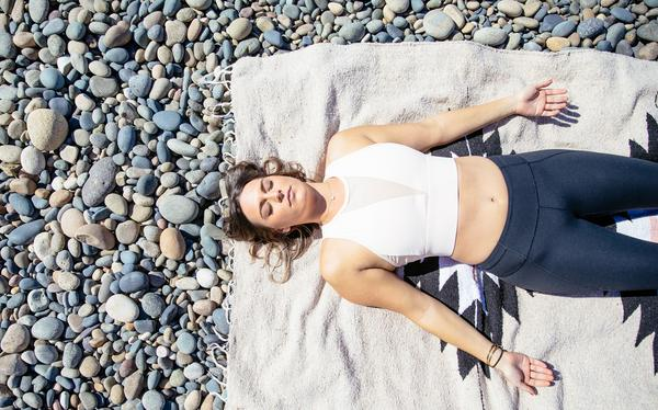 Woman lying on the beach and meditating