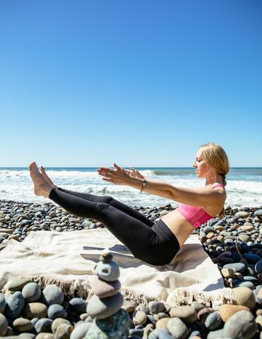 Navasana yoga pose on the beach